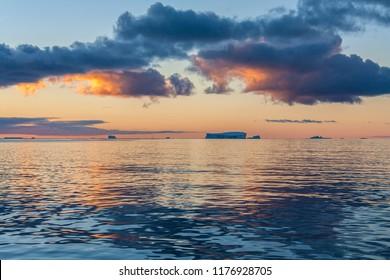The Midnight sun over the icebergs of the Drake Passage near the Antarctic Peninsula in Antarctica.