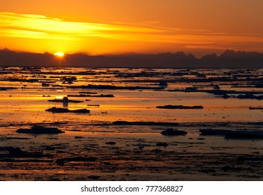 The midnight sun and sea ice in the Arctic Ocean off the north east coast of Greenland