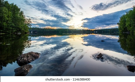 Midnight sun with water reflection at lake in Finland