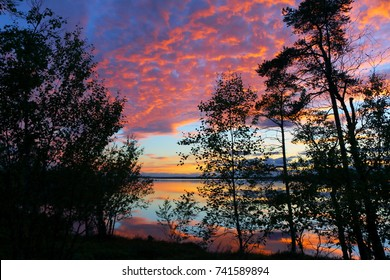 midnight sun with water reflection at lake inari in finland, scandinavia, europe