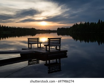 Midnight sun.Empty footbridge with a bench on a lake in Lapland.