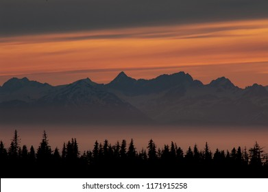 Midnight sunset glow over mountain peaks in foggy Kachemak Bay and Cook Inlet, Alaska.