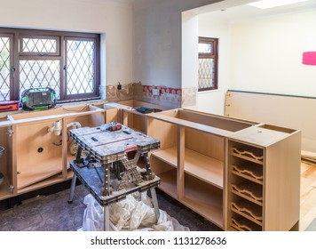 Midpoint in a kitchen renovation project. Cupboards and wine rack ready to fit doors and work surface. Tools, worktable and dust sheets ready for use.