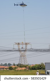 MIDRAND, SOUTH AFRICA-FEBRUARY 13 2016: ABell 407 helicopter  lowering insulators to the top of a tower during insulator replacement on 400kV Eskom power lines