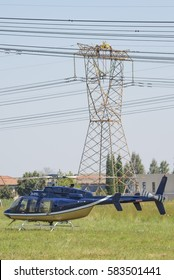 MIDRAND, SOUTH AFRICA-FEBRUARY 13 2016: Linesman work on 400kV lines with a Bell 407 helicopter in the foreground.