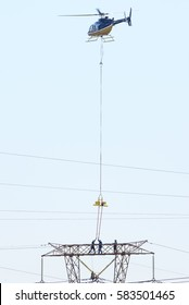 MIDRAND, SOUTH AFRICA-FEBRUARY 13 2016: Linesman doing powerline maintenance on 400kV lines being supported by a Bell 407 helicopter.