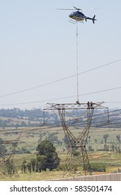 MIDRAND, SOUTH AFRICA-FEBRUARY 13 2016: Helicopter lowering a linesman onto a tower  during insulator maintenance on 400kV lines