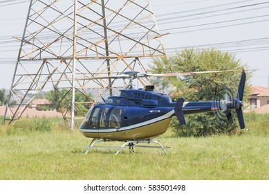 MIDRAND, SOUTH AFRICA-FEBRUARY 13 2016: An Eskom Bell 407 helicopter landed next to 400kV lines at Midstream Estates in Midrand