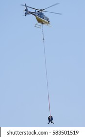MIDRAND, SOUTH AFRICA-FEBRUARY 13 2016: Two linesman being lowered from of a Bell 407 helicopter  during insulator replacement on 400kV Eskom power lines