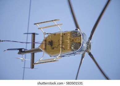 MIDRAND, SOUTH AFRICA-FEBRUARY 13 2016: Helicopter pilot looking down out of a Bell 407 helicopter  during insulator maintenance on 400kV lines