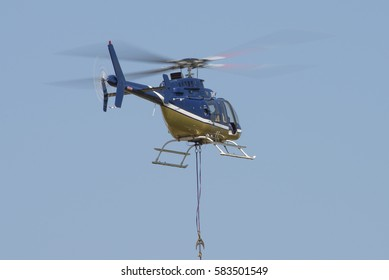 MIDRAND, SOUTH AFRICA-FEBRUARY 13 2016: An Eskom Bell 407 helicopter performing powerline maintenance on 400kV lines next to Midstream Estates in Midrand