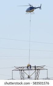 MIDRAND, SOUTH AFRICA-FEBRUARY 13 2016: Linesman doing powerline maintenance on 400kV lines receiving equipment from a Bell 407 helicopter.