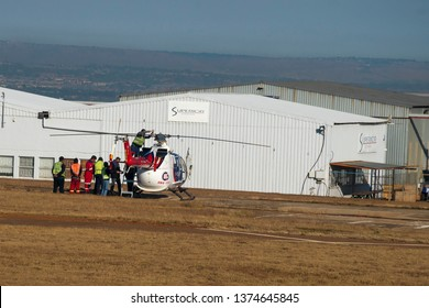 MIDRAND, SOUTH AFRICA-JULY 21 2018: Many mechanics repair a helicopter at Grand Central airport in hi-vis clothing.