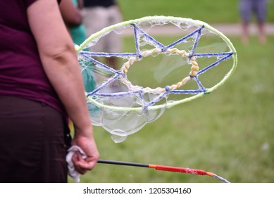 Midriff of unrecognizable woman dressed in purple holding an oversized bubble net.  Blurred background of outdoor park.