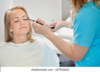 Midsection of beautician applying eye shadow to young woman at parlor