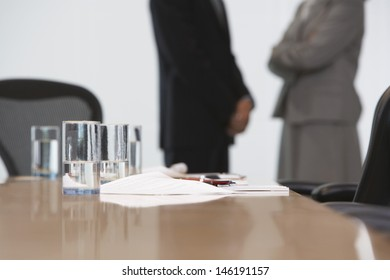 Midsection of a business couple standing with focus on conference table