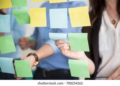 Midsection Of Business People Sticking Adhesive Notes On Glass
