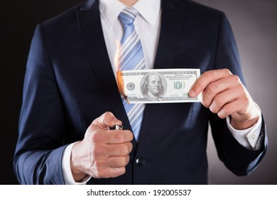 Midsection of businessman burning money against black background