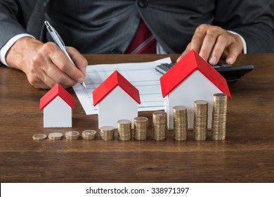 Midsection of businessman calculating tax by different size houses and stacks of coins on table