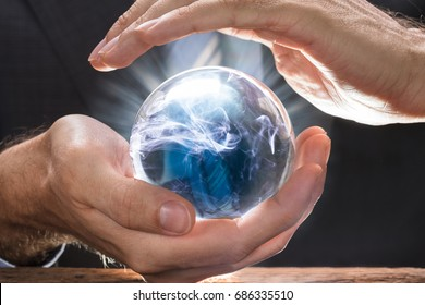 Midsection of businessman covering crystal ball with swirling smoke at wooden table