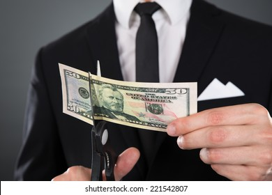 Midsection of businessman cutting dollar bill with scissors over gray background