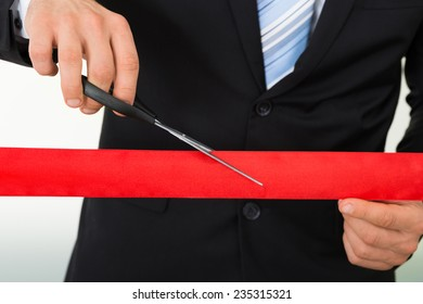 Midsection of businessman cutting red ribbon with scissors over white background