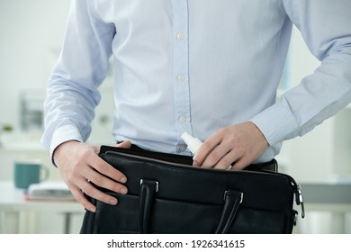 Midsection of businessman in formalwear putting sanitizer in small plastic bottle with spray into black leather handbag by his workplace