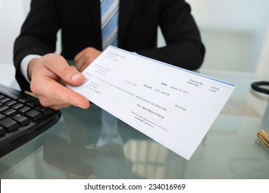 Midsection of businessman giving cheque at desk in office