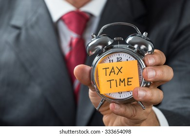 Midsection of businessman holding alarm clock with tax time reminder note