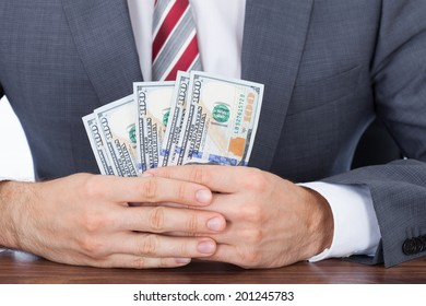 Midsection of businessman holding fanned banknotes at desk