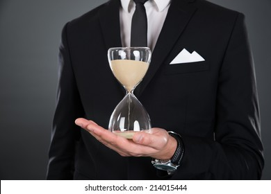Midsection of businessman holding hourglass isolated against gray background