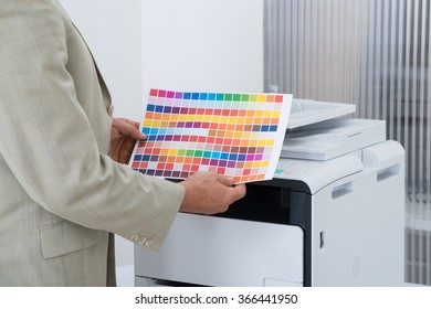 Midsection of businessman holding multi colored paper by printer in office