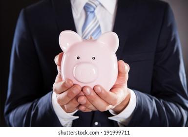 Midsection of businessman holding piggybank against black background