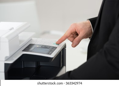 Midsection of businessman operating printer in office