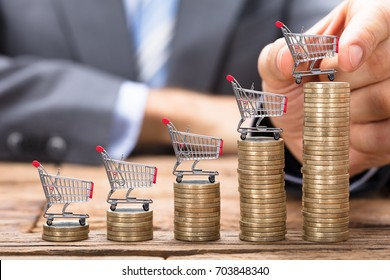 Midsection of businessman placing shopping cart on stacked coins in increasing order