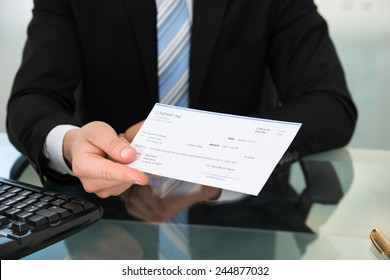 Midsection of businessman showing cheque at desk in office