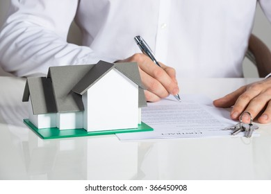 Midsection of businessman signing house contract at office desk