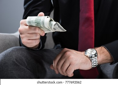 Midsection of businessman sitting in armchair  and holding money in hand, isolated on gray