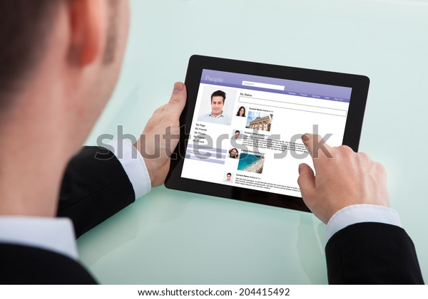 Midsection of businessman surfing social networking site on digital tablet in office