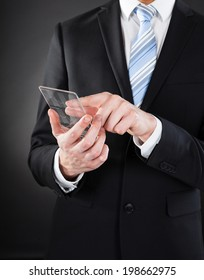 Midsection of businessman using futuristic smartphone against black background
