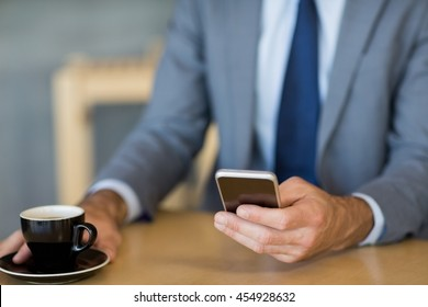 Mid-section of businessman using mobile phone while having a cup of tea in restaurant