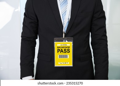 Midsection of businessman wearing backstage pass in office