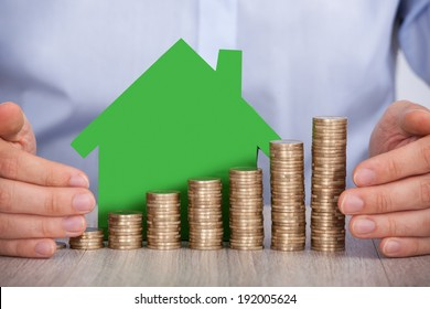 Midsection of businessman's hands protecting stacked euro coins and house model in office