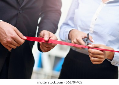 Midsection of businesspeople cutting the ribbon