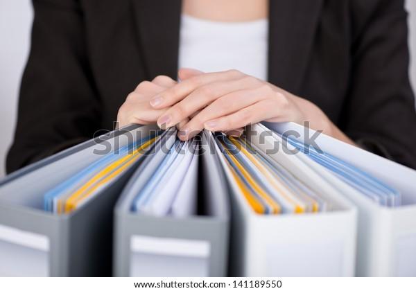 Mittelteil der Geschäftsfrau mit Bindemitteln im Büro