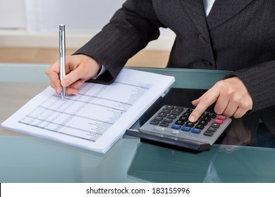 Midsection of businesswoman calculating tax at desk in office