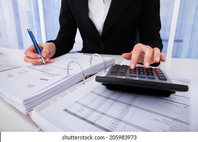 Midsection of businesswoman calculating tax at office desk