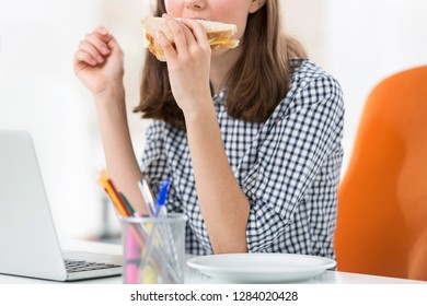 Midsection of businesswoman eating sandwich while working in office