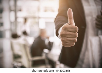 Midsection of businesswoman showing thumbs up sign in office with copy space