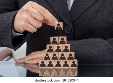 Midsection of businesswoman stacking wooden team blocks at table